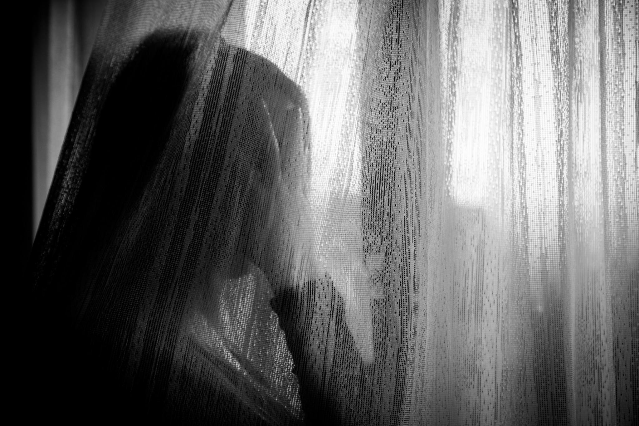 Ensam ledsen kvinna stirrandes ut genom fönster.