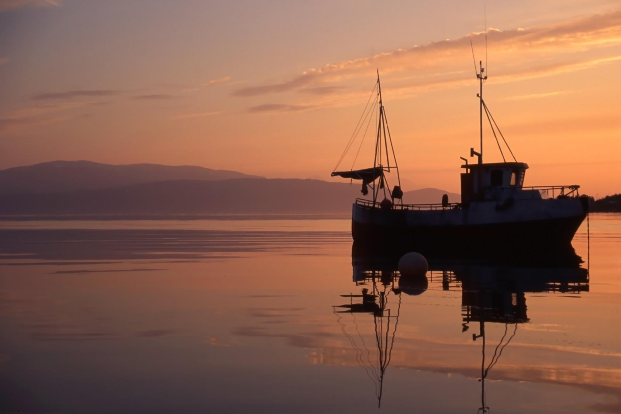 Fiskebåt i stilla vatten under soluppgång.