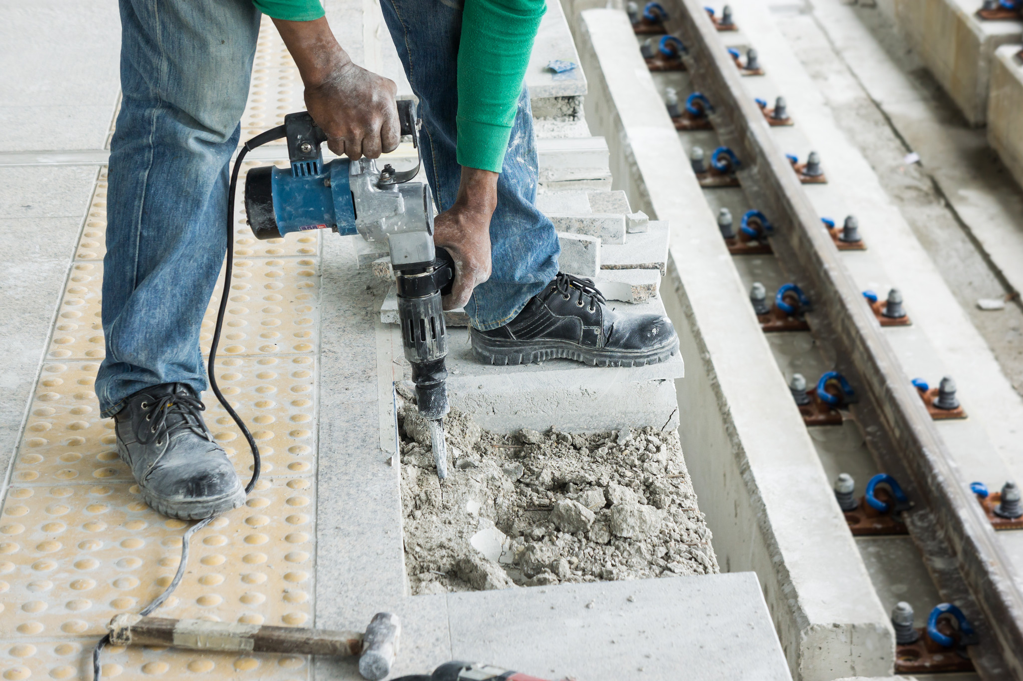 Arbetare med slagborr krossar cement