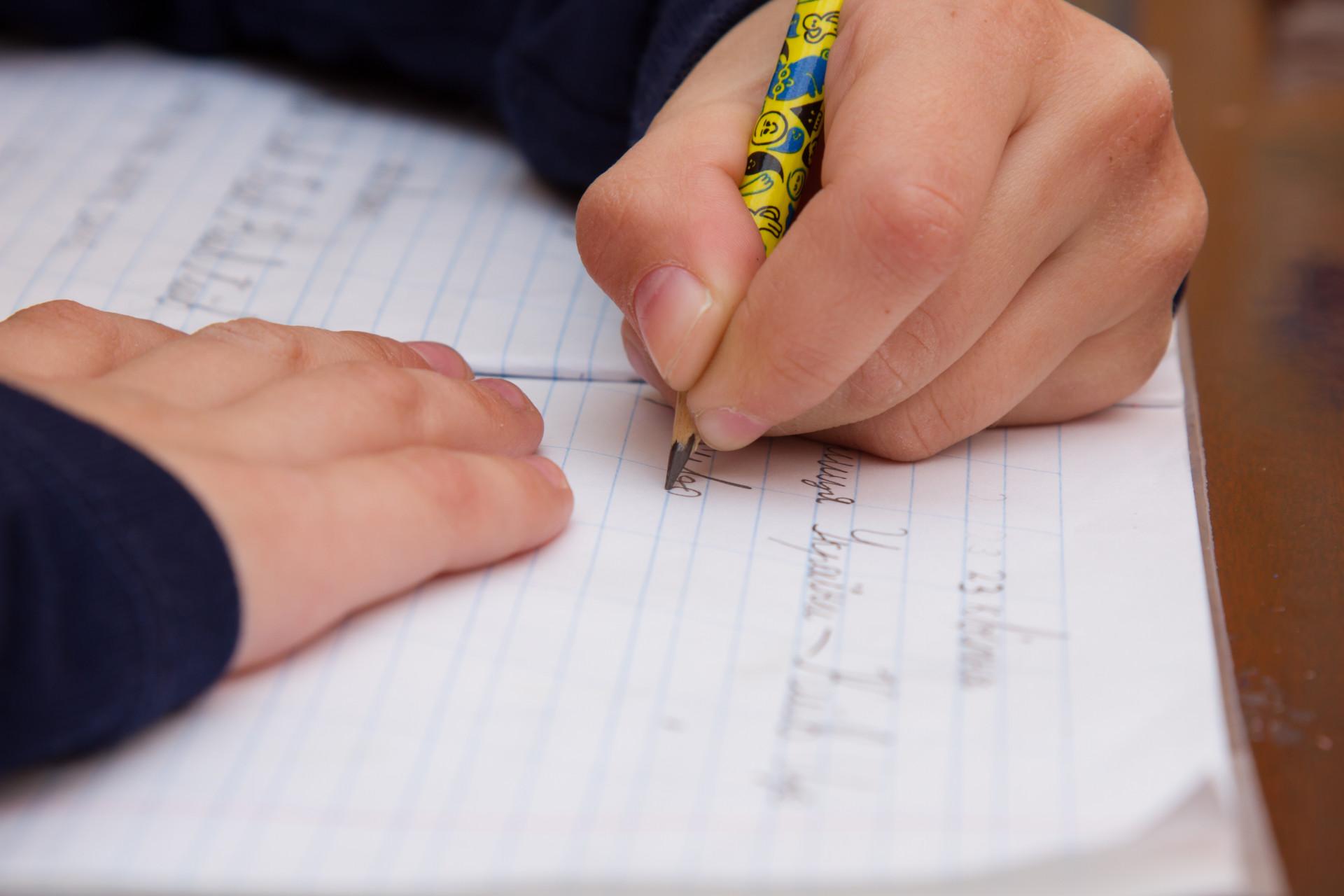 Barn skriver sina läxor med blyertspenna mot pappersblock.