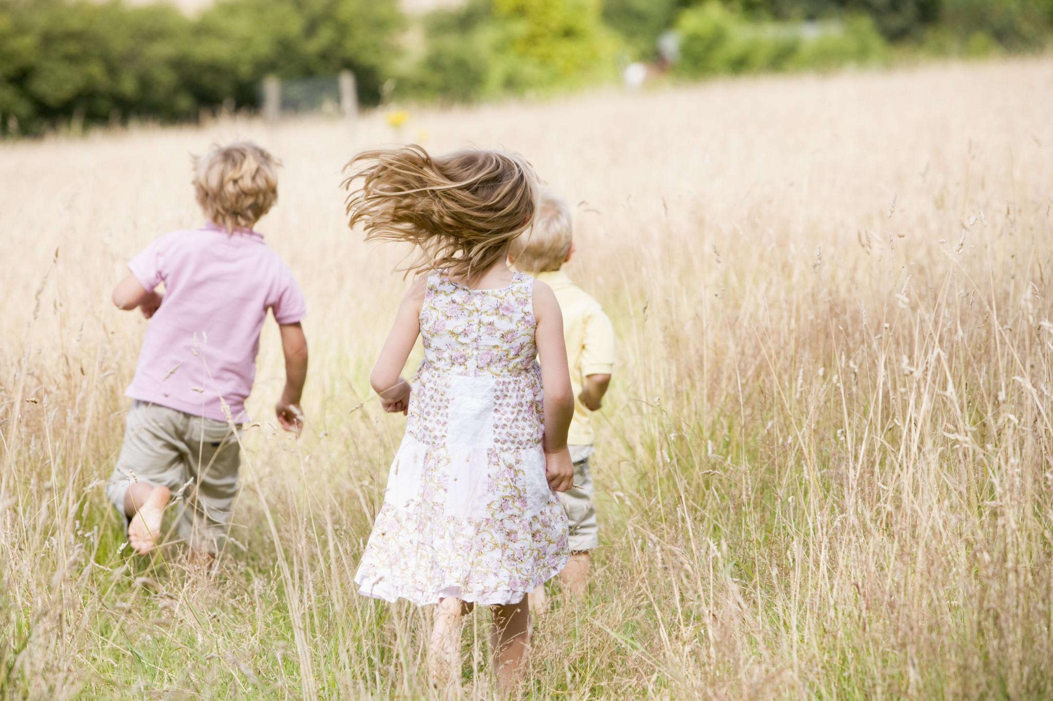 Tre mindre barn springandes på äng.