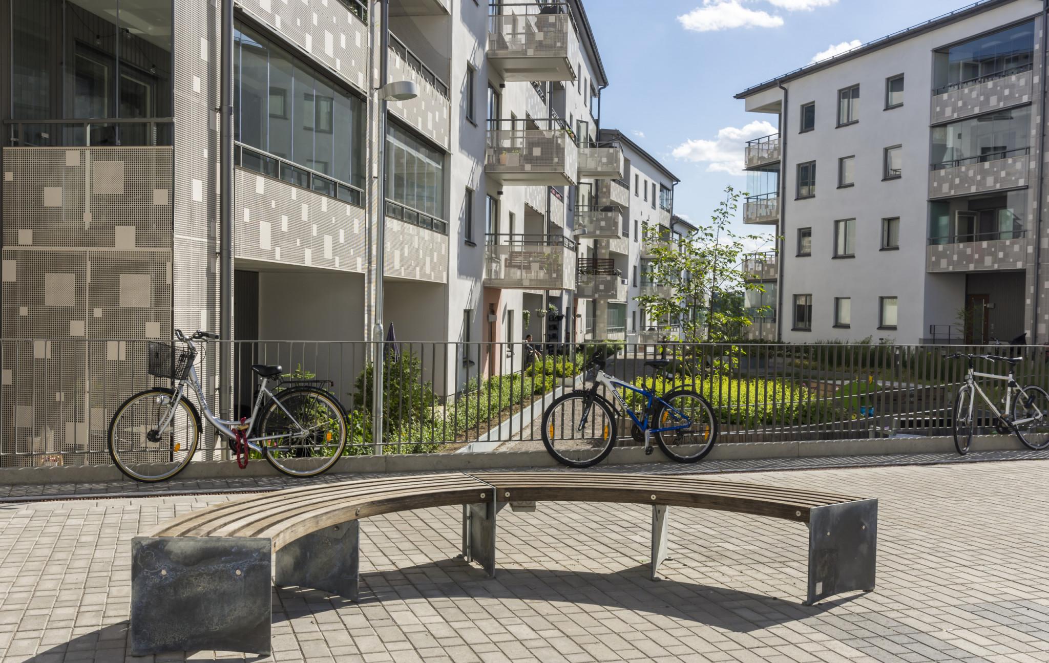 Nyproducerade och fräscha hyresrätter med grönområde och parkerade cyklar.