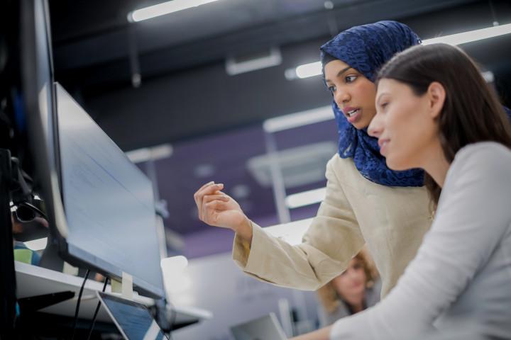 Unga mjukvaruutvecklare använder datorer för att koda.