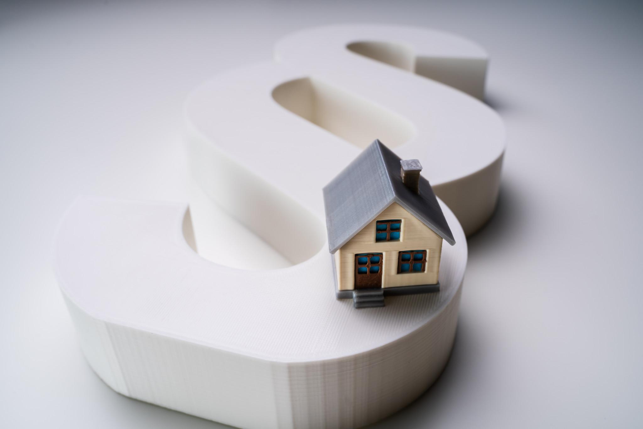 Närbild på modellering av hus i anslutning till paragraf-symbol.