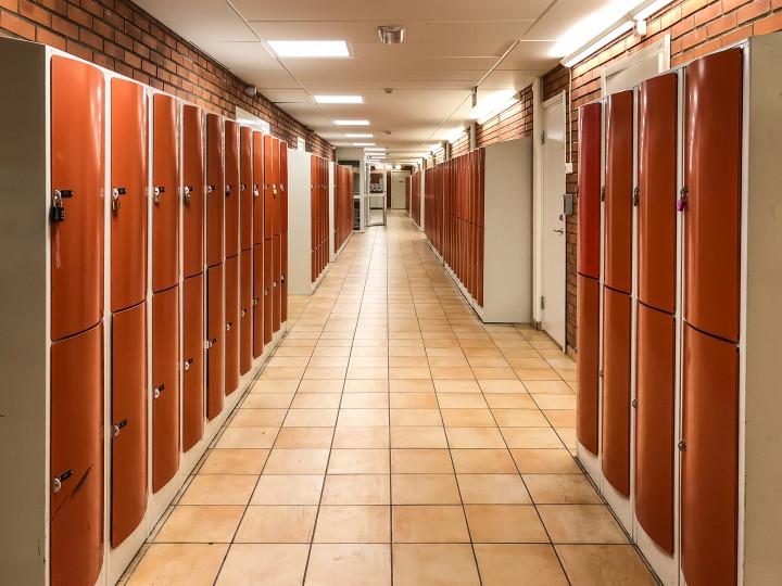 Lång skolkorridor med röda skåp
