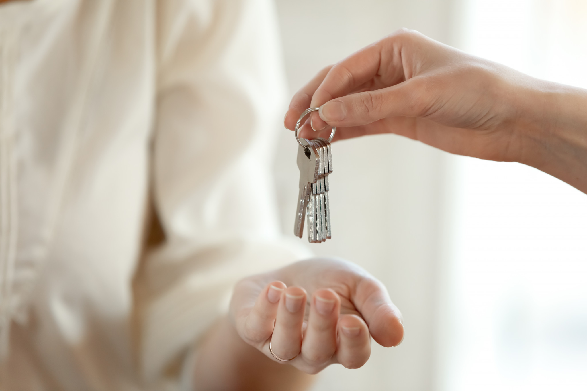 Från hand till hand. Närbild på kvinnlig mäklare som sträcker över nycklar till ung kvinna.