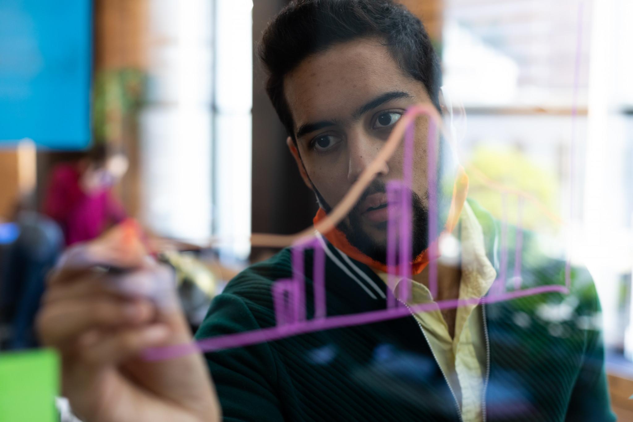 Man ritar matematiska tabeller på glastavla