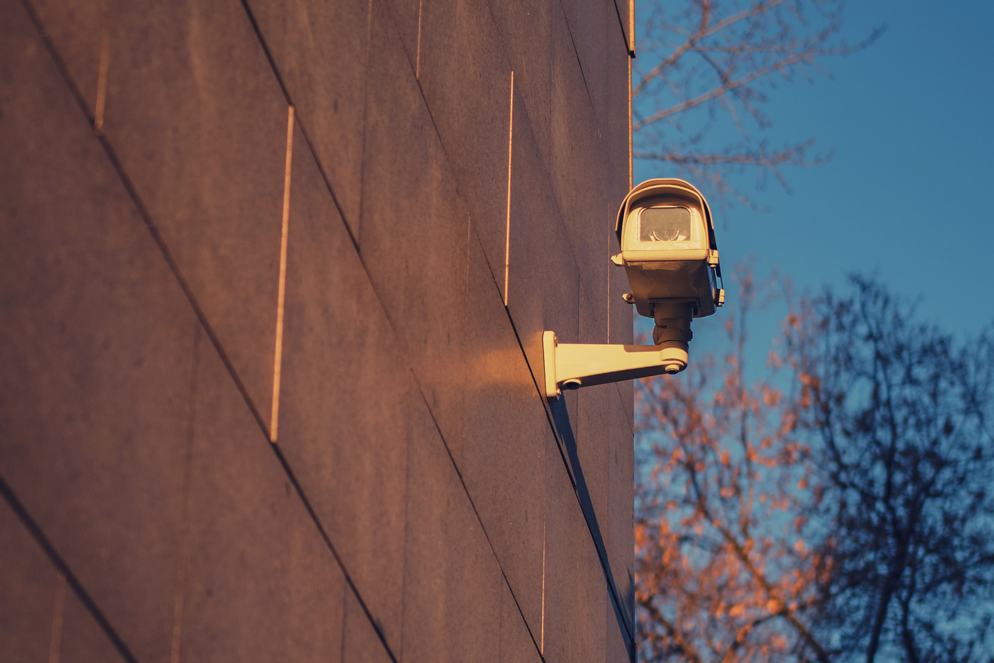 Övervakningskamera fäst på fastighet. Närbild med vy över urbant område under solnedgång.