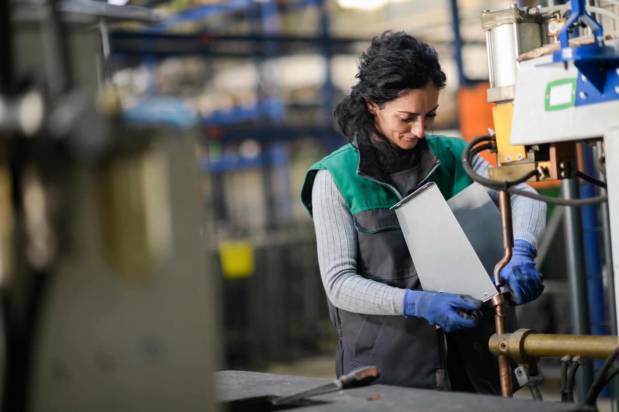Kvinna arbetandes i modern metallfabrik.