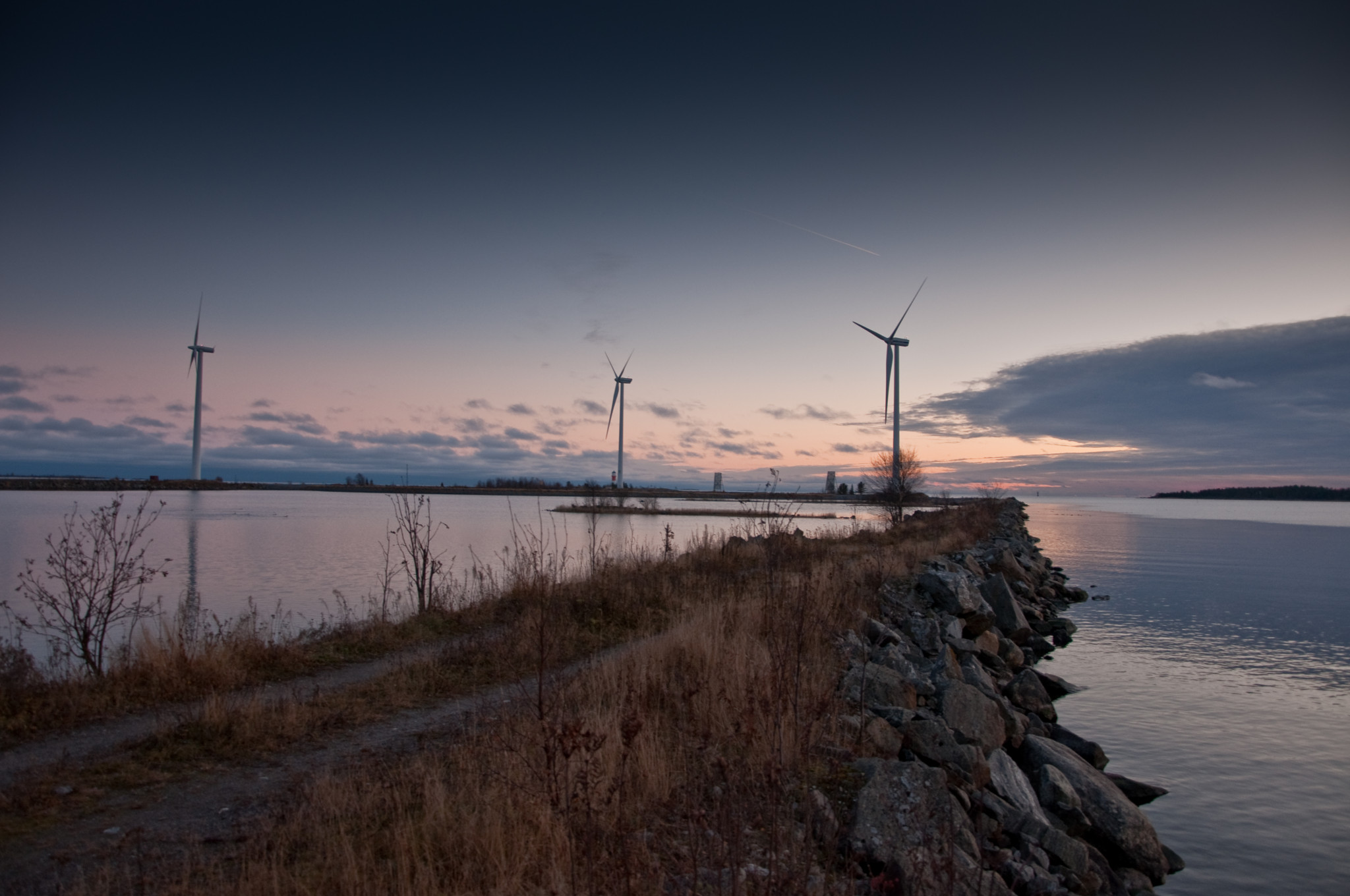 Vindkraftverk ute tillhavs i solnedgång