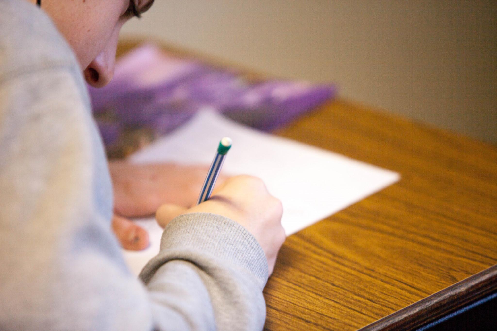Ung elever sittandes koncentrerad vid skolbänk.