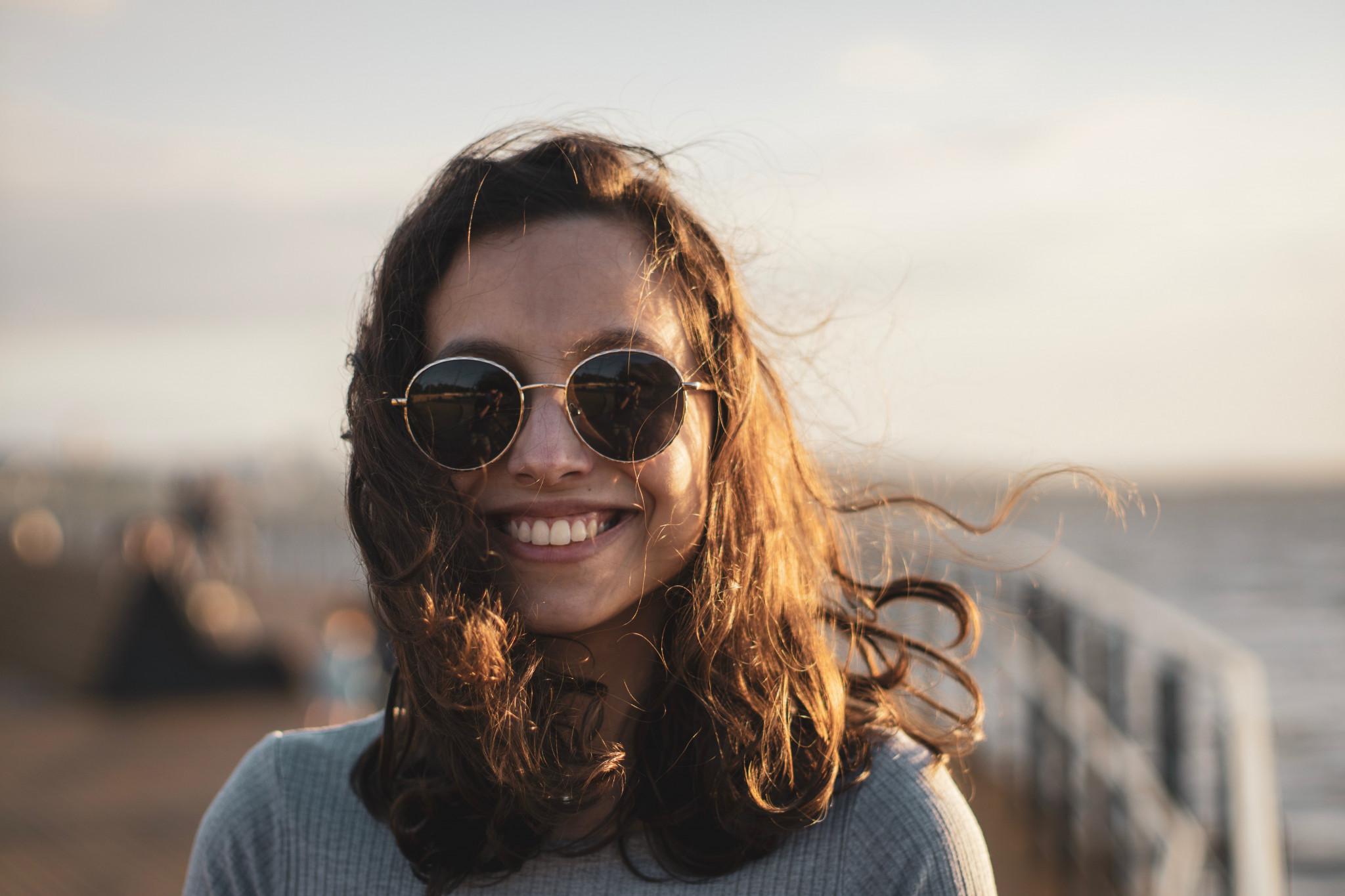 Ung kvinna med solglasögon ler med kust i bakgrunden.