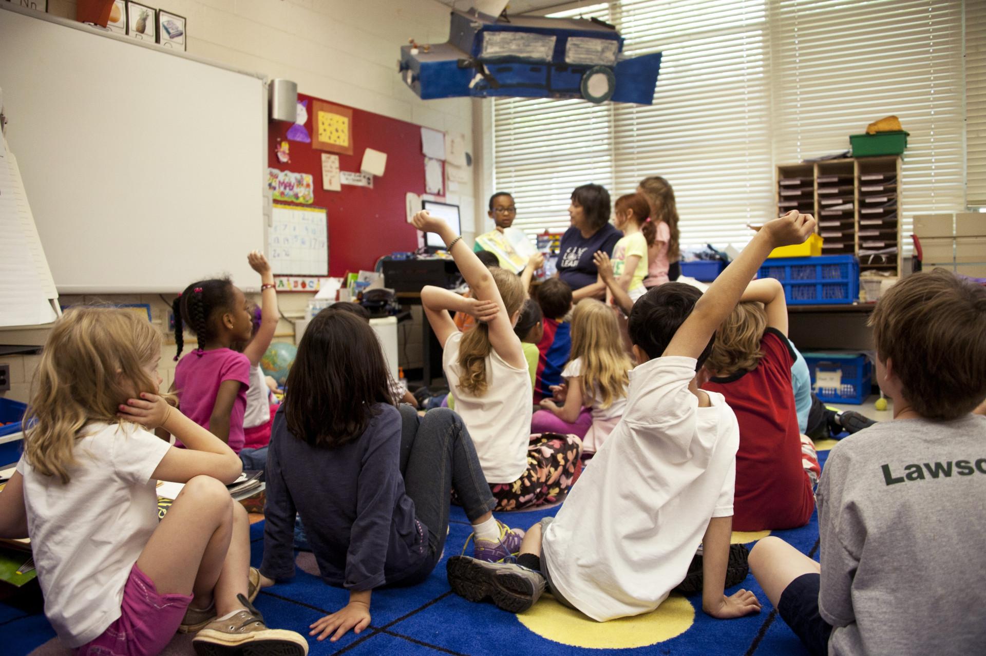 Grundskoleelever i klassrum sittandes på golv.