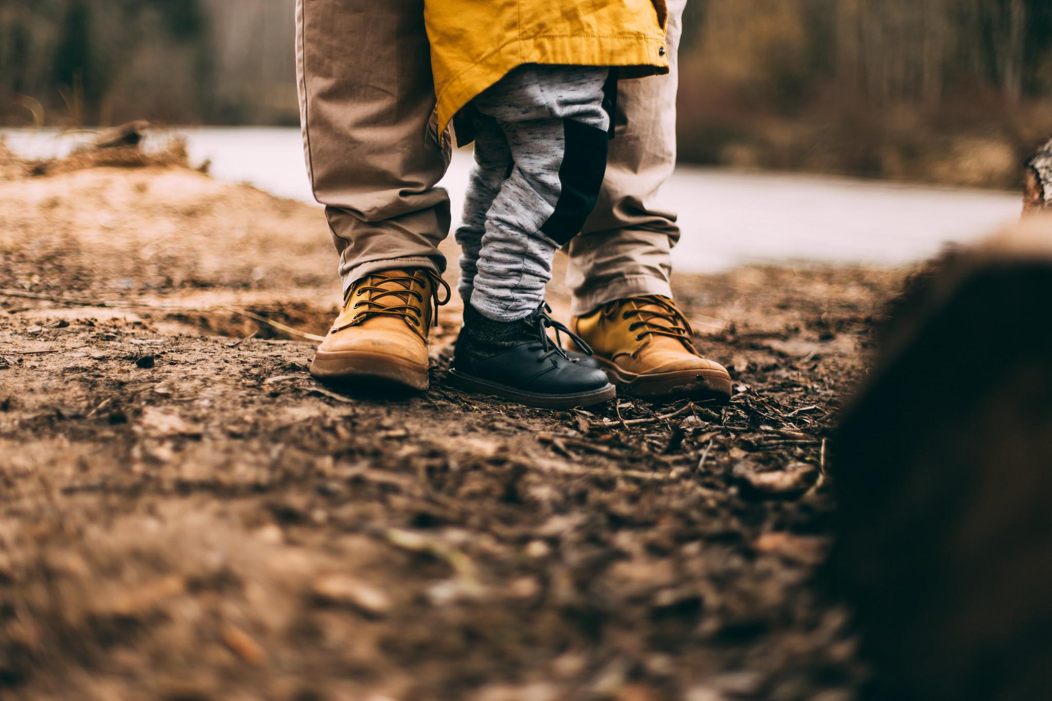 Förälder och barn med boots i fokus ståendes i skogsmiljö.