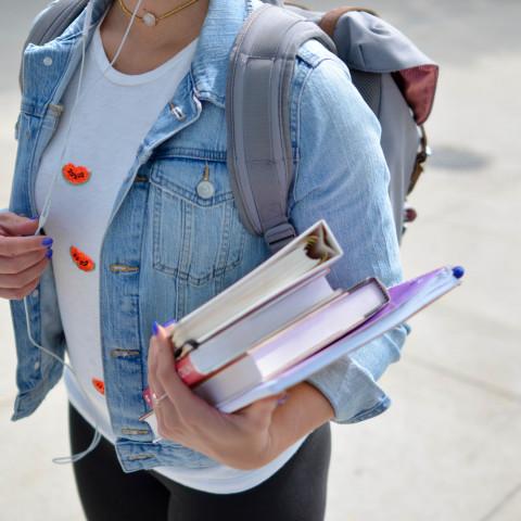 Student hållandes i kurslitteratur och anteckningsblock