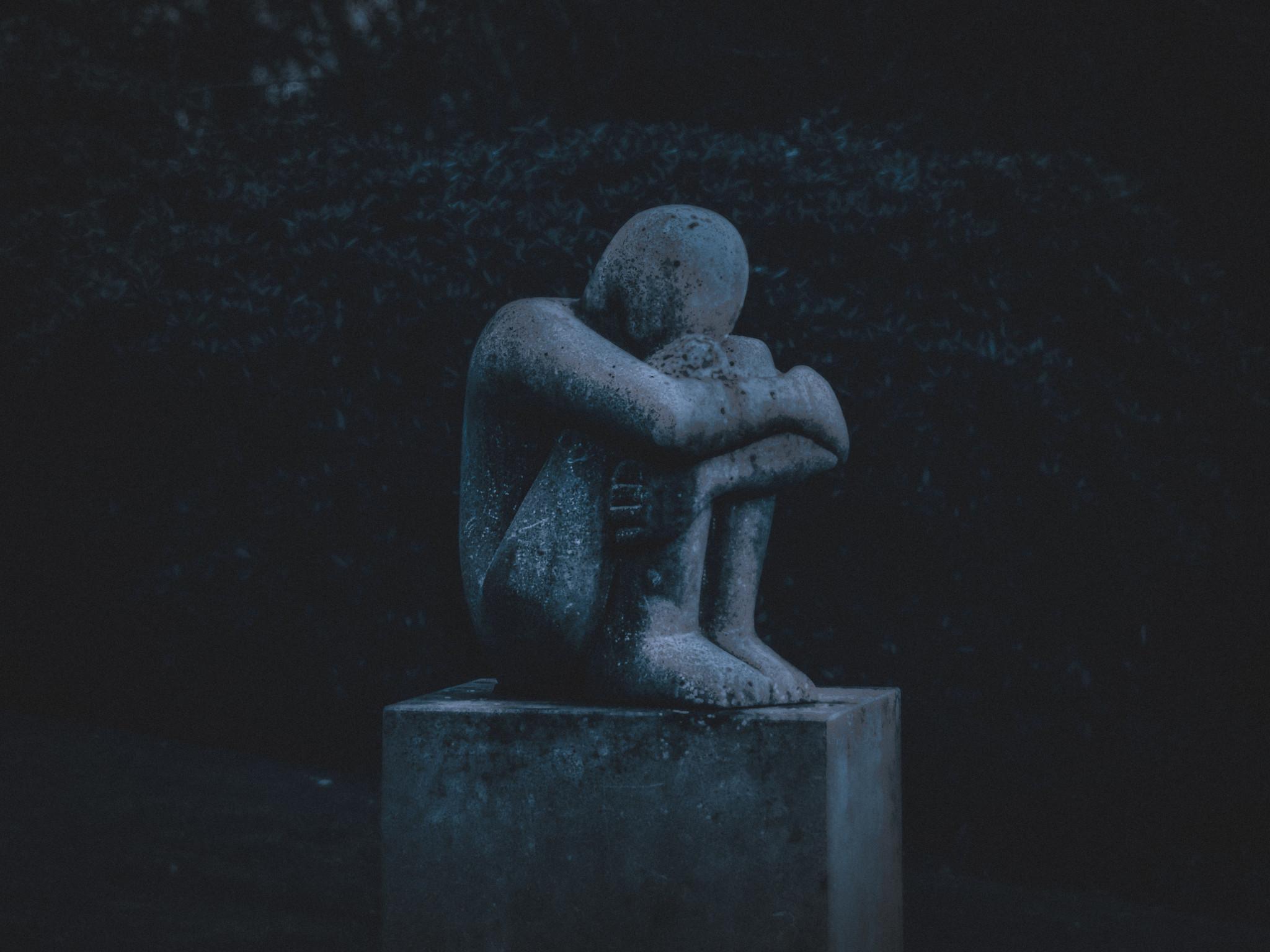 Staty av hopkurad person som symboliserar psykisk ohälsa. Mörk siluett.
