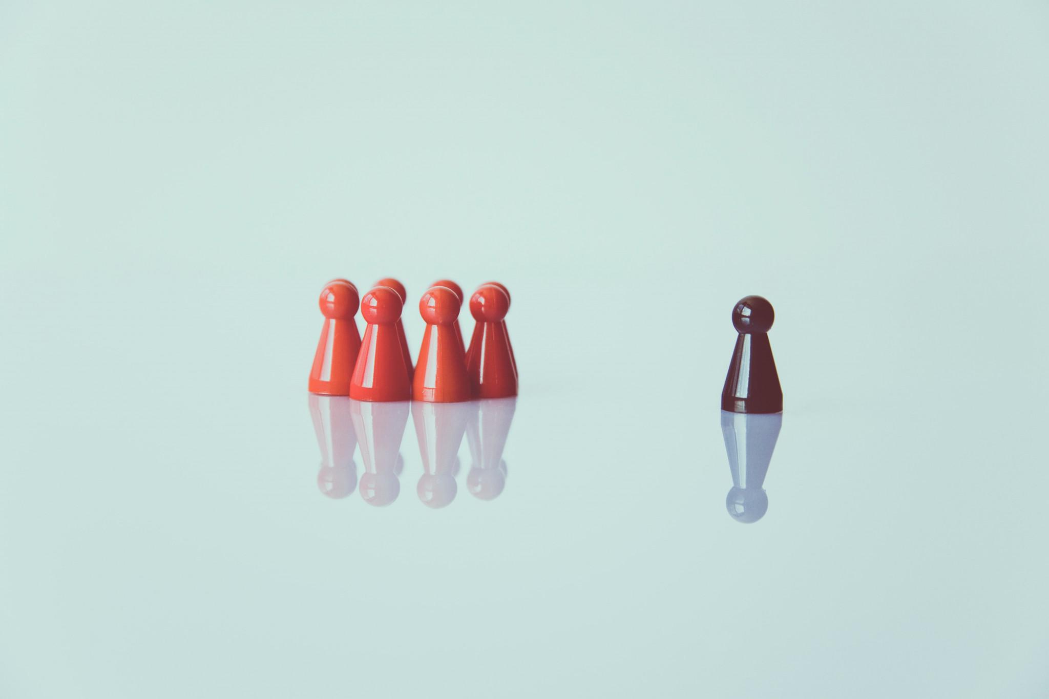 Röda sällskapsspels figurer i klunga med en ensam mörk spelbjäs.