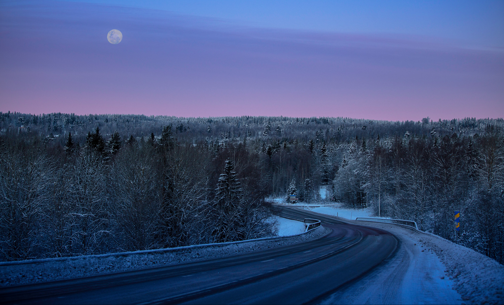 Snötäckt landsväg i solnedgång.