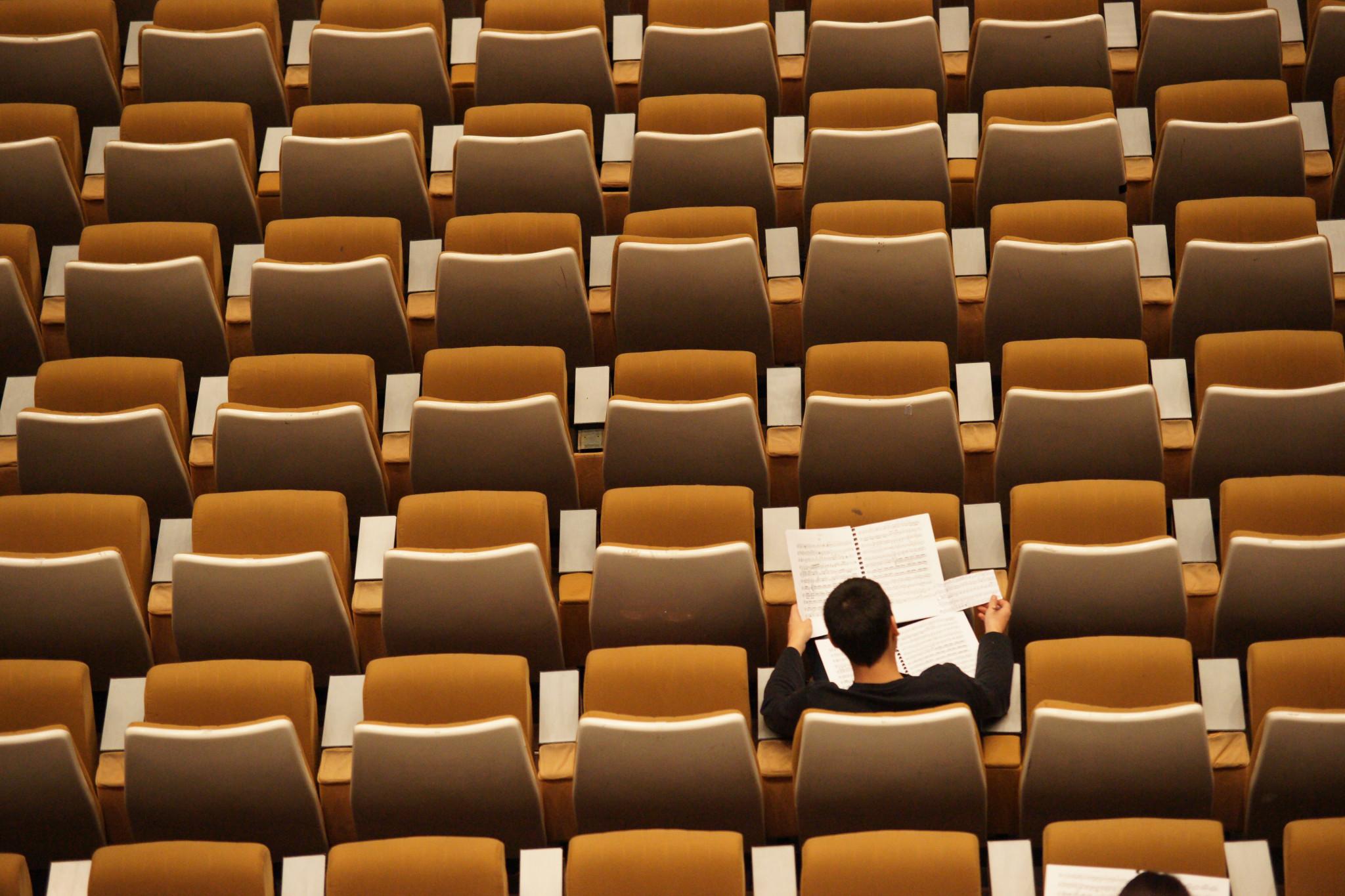 Ensam manlig student studerandes vid stor aula.
