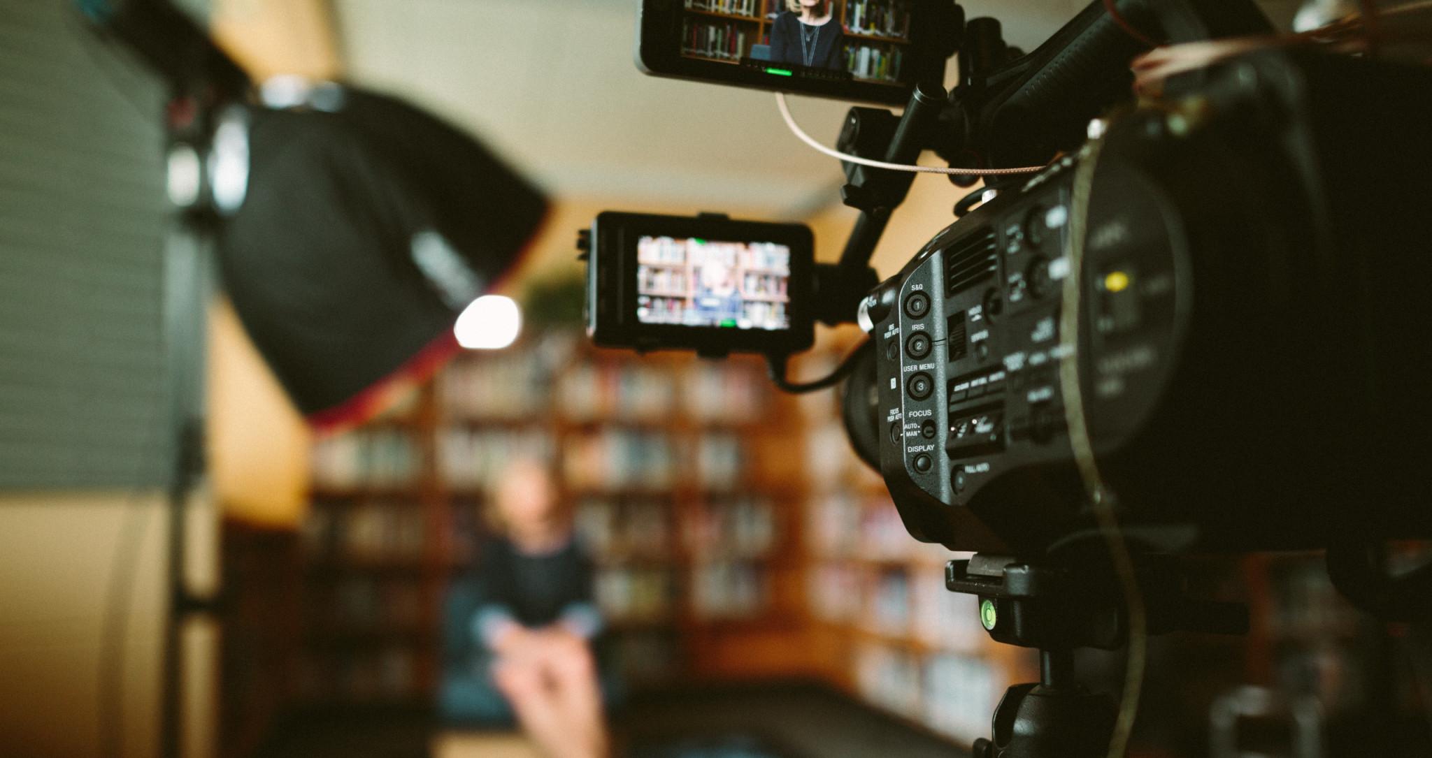 Bakom kulisserna under inspelning av intervju. Kamera i fokus, intervjuobjekt ur fokus.
