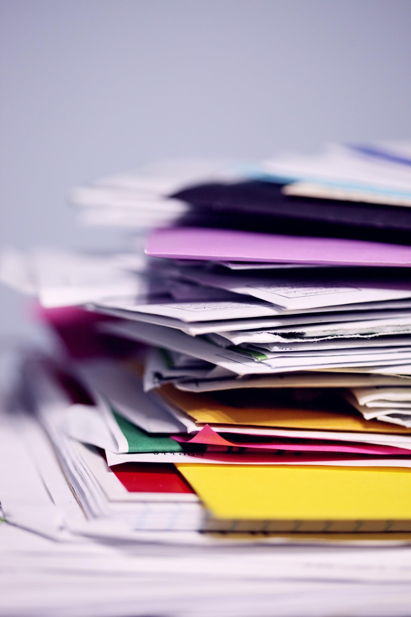 Anteckningsblock, dokument och mappar staplade på hög.