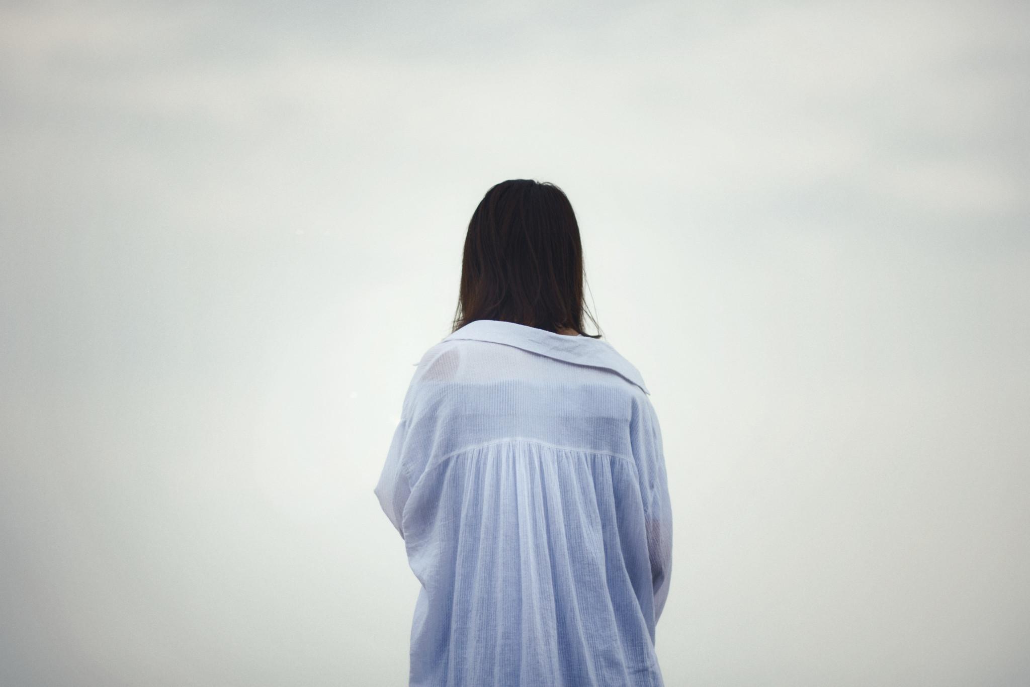 Mörkhårig person blickar ut mot mulen horisont iklädd oversized skjorta.